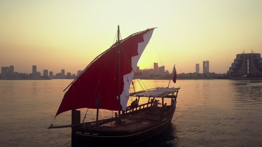 Manama, Bahrain - October 2018: Drone view of the Traditional Arabic Dhow with Bahrain flag branded sail during the sunset time in front of Manama Skyline