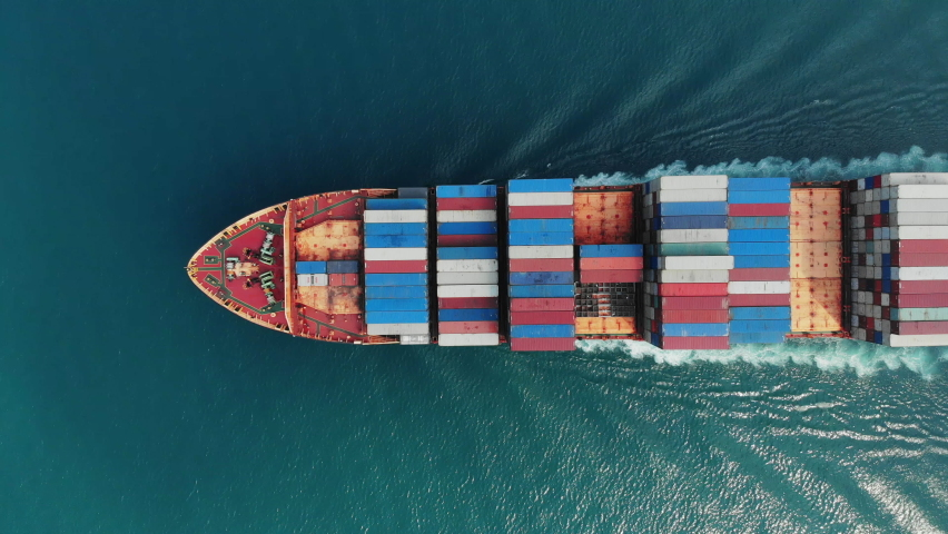 Aerial top view of smart cargo ship carrying container and running very fast for export cargo from container yard port to custom ,Contrail line in the ocean by large ship very fast.  | Shutterstock HD Video #1063952983