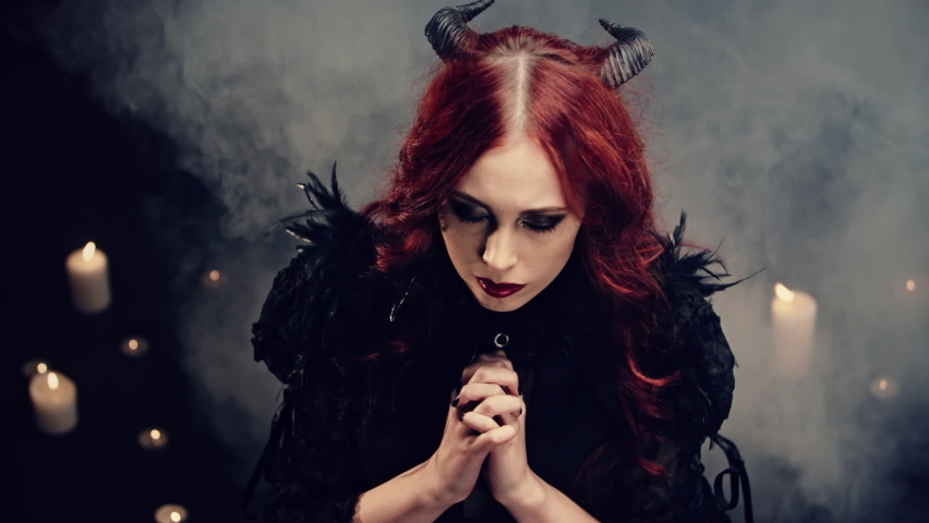 Red-haired girl witch with black horns sitting on floor in candlelight and praying with folded hands. Scary demon doing witchcraft. Halloween mystery rite. Ritual of Occultism or esoterics concept.   Shutterstock HD Video #1063961242