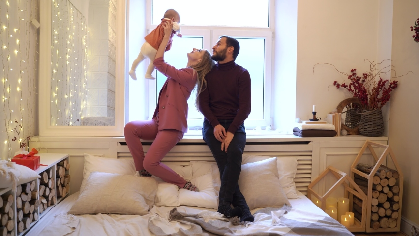 Full body father and mother smiling and playing with baby daughter while resting near window on bed in cozy bedroom #1063964356