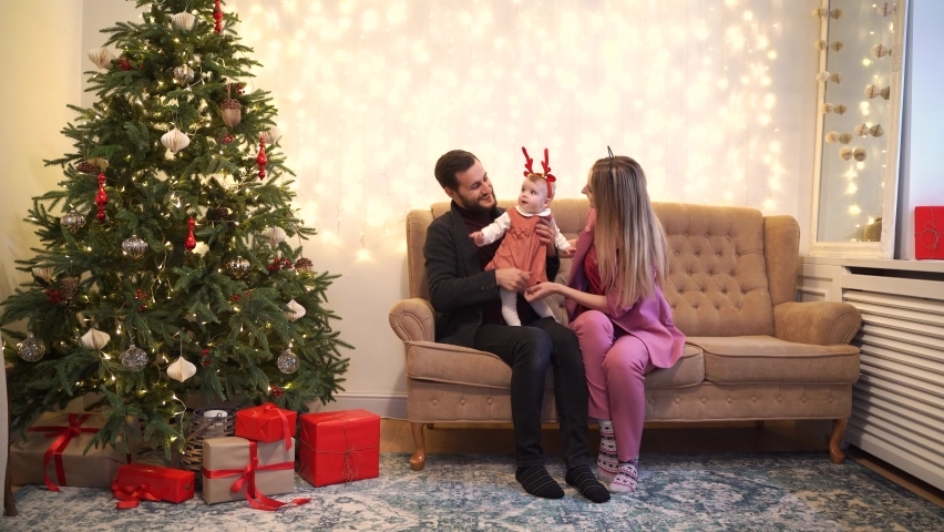 Full body father and mother playing with baby while sitting on comfortable couch near decorated Christmas tree and presents in cozy living room #1063964437