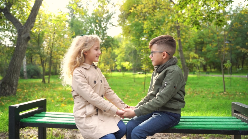Little couple sitting on bench in autumn park. Happy boy and girl smiling and looking at each other while sitting on bench during break in autumn park #1063964518