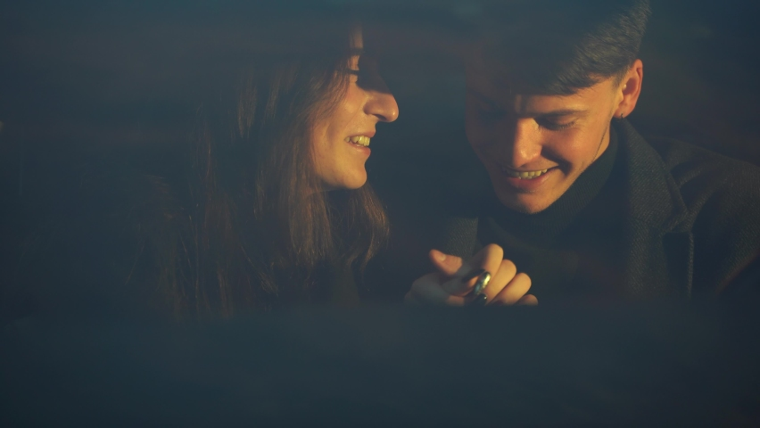 Cheerful boy smiling and embracing girlfriend while sitting inside vehicle during romantic date in evening #1063966420