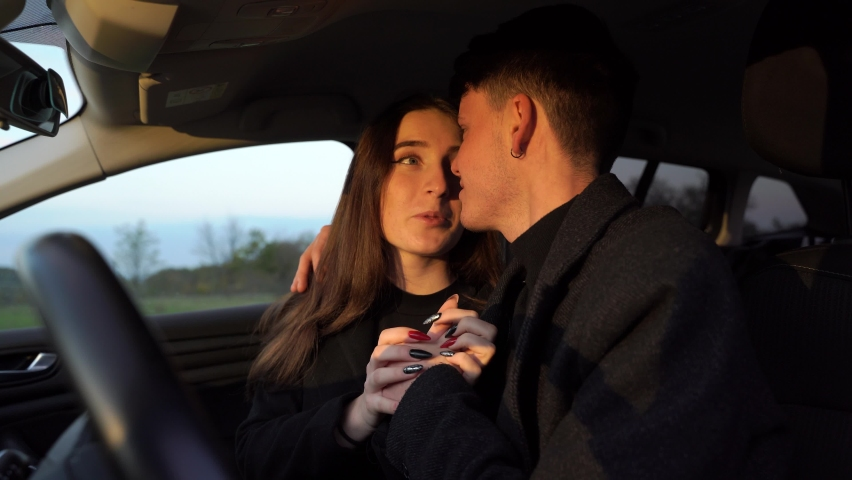 Cheerful young man smiling and embracing girlfriend while sitting inside vehicle #1063966426