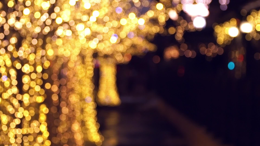 Abstract bokeh background of blurred decorated Christmas trees in golden garland on street of evening city. New Year holidays background of trees with glowing and sparkling lights at dusk in defocus. Royalty-Free Stock Footage #1063969828