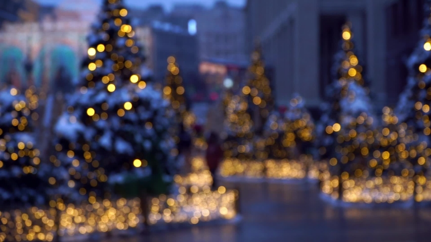 Bokeh background of blurred decorated Christmas trees in golden garland on street with people of evening city. Eve of Christmas and New Year holidays with fir-trees at dusk in defocus. Royalty-Free Stock Footage #1063969831