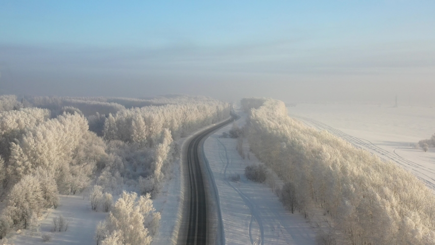 Aerial video view from drone of a Sunrise over snowy winter road. Birch forest under hoarfrost in winter season. Siberia, Russia