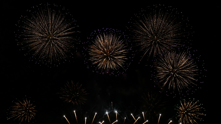 4K. loop seamless of real beautiful fireworks background during new year's eve countdown celebration, real golden shining fireworks festival in the sky at night with colorful. glowing fireworks show. Royalty-Free Stock Footage #1063978351