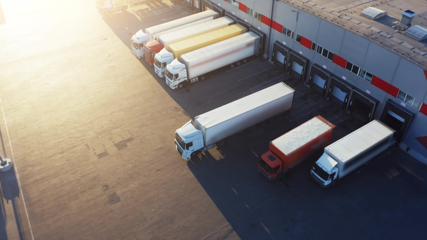 Trucks with semi-trailers stand on the parking lot of the logistics park with loading hub and wait for load and unload goods at warehouse ramps at sunset. Aerial view Royalty-Free Stock Footage #1063979203