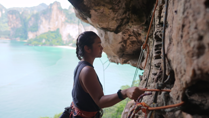 Confidence Asian woman climber preparing for climbing up the rocky mountain with safety rope and harness at tropical island. Healthy female enjoy active lifestyle and extreme sport in holiday vacation | Shutterstock HD Video #1063981516