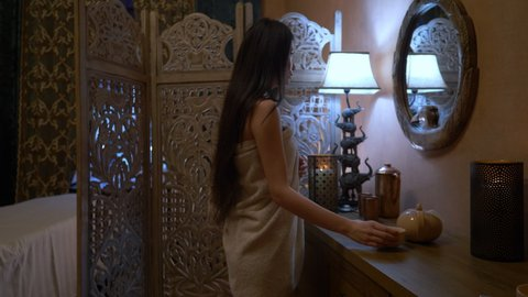 young asian woman getting Ayurveda treatment in spa salon, woman in towel at the mirror, relaxation healthcare concept. High quality 4k footage
