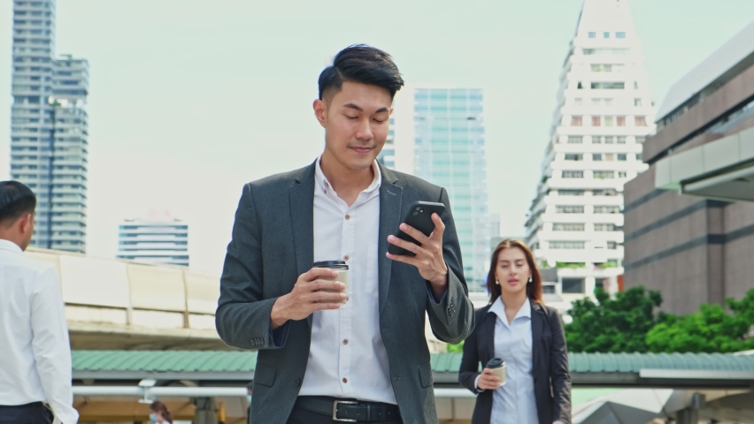 Asian young smart businessman using smartphone in city. The man holding phone walking outdoor to working office with smile face. Telecommunication and mobile network for business concept. Royalty-Free Stock Footage #1063999291