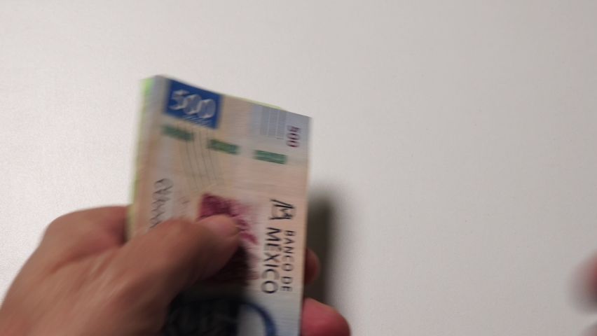 A hand is counting and giving 200 pesos and 500 pesos mexicanos billets Royalty-Free Stock Footage #1064004373