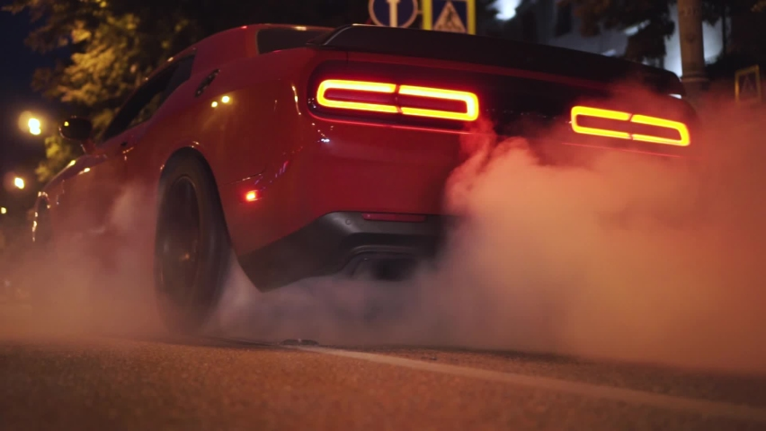Car start with smoke on wheels. Footage. Red modern drag sport auto burning tire at city street. Royalty-Free Stock Footage #1064009665