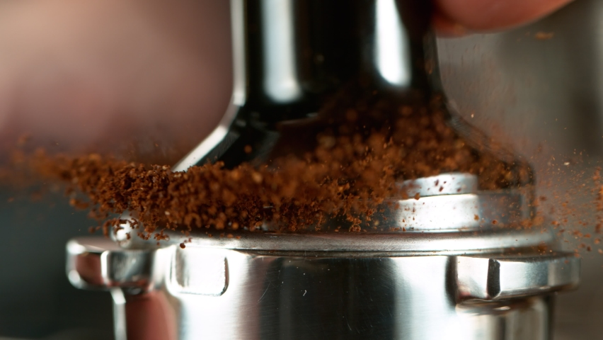 Close-up Slow Motion of Grinder Stuffing Roasted Coffee from Coffee Machine. Filmed on High Speed Cinematic Camera at 1000 fps.