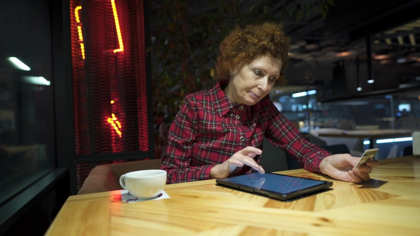 Senior woman ordering Christmas gifts online on digital tablet in coffee shop. Mature buyer holding tablet pc and credit card. Elderly woman shopping online. Online personal finance. Black Friday.