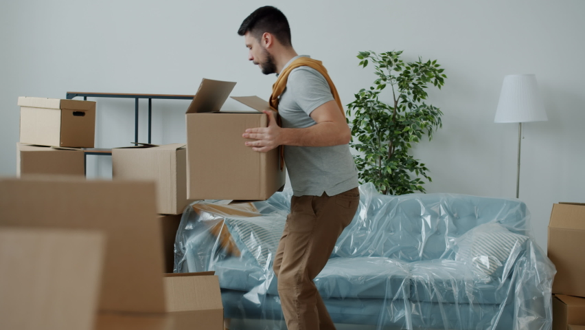 Slow motion of young man carrying boxes to new house then touching back feeling pain suffering from backache. Relocation and health problems.