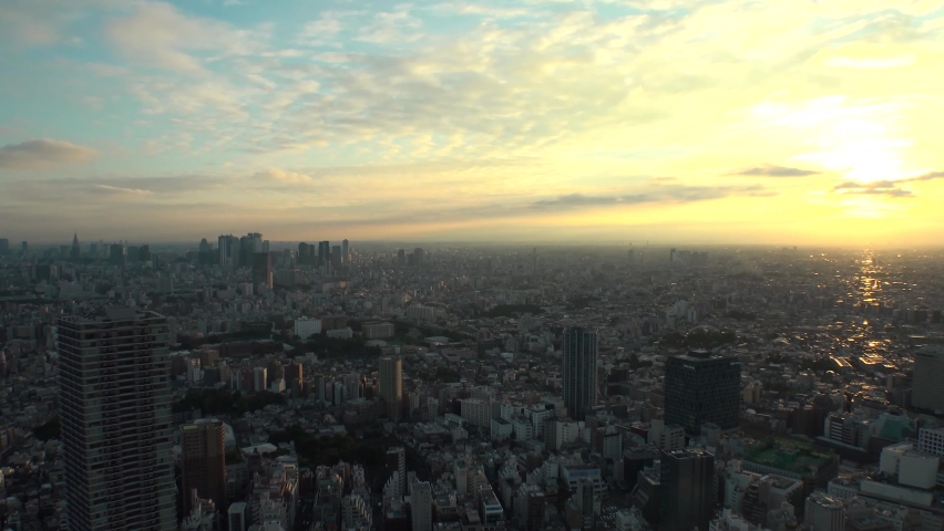 TOKYO, JAPAN : Aerial high angle sunrise CITYSCAPE of TOKYO. View of buildings around Shinjuku and Nakano ward. Japanese urban metropolis and nature concept. Time lapse zoom out shot night to morning.