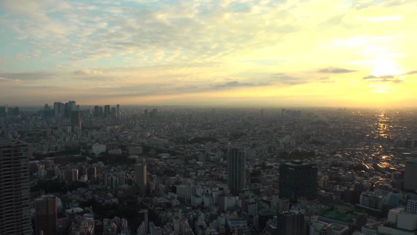 TOKYO, JAPAN : Aerial high angle sunrise CITYSCAPE of TOKYO. View of buildings around Shinjuku and Nakano ward. Japanese urban metropolis and nature concept. Time lapse tracking shot night to morning.