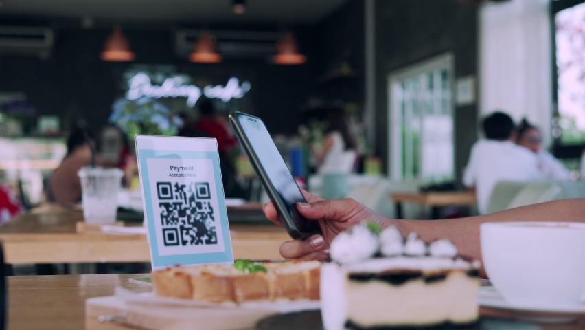 Women using their phones for scanning to pay for coffee and cake on cafe. Mobile scanning system oline for pay money . Concept technology for pay by scan QR code. Royalty-Free Stock Footage #1064025844