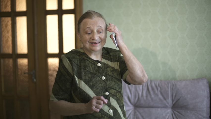 Grandma emotionally talks on her cell phone and shows super. Elderly woman smiling talking on a smartphone and showing super. Close-up portrait of the senior woman talking on the phone