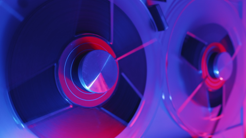 Reel to reel tape recorder playing ultra red blue neon light. Rotating vintage music player close up. Retro tape. Spinning reels metallic color with red disc. Popular Disco Trends 60s, 70s, 80s, 90s. | Shutterstock HD Video #1064038630