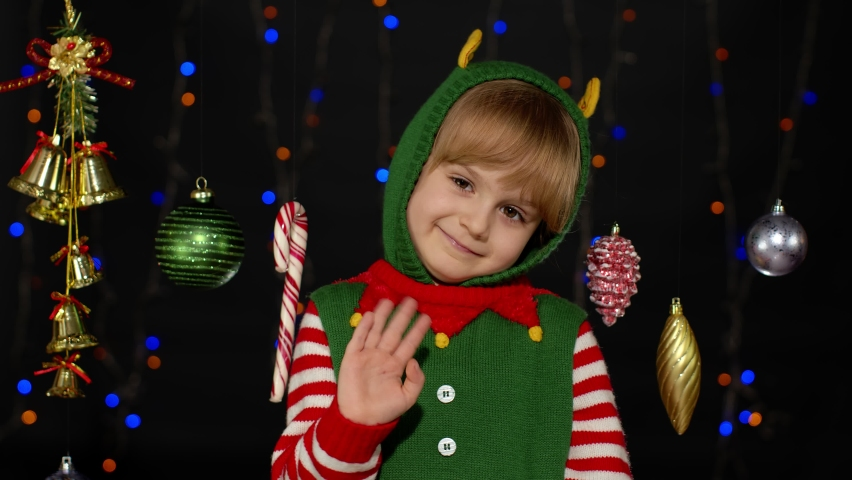 Teen kid girl in Christmas elf Santa helper costume waving greeting with hand as notices someone. Hello, hi, greetings gesture. Small child smiling, hugs, fooling around. New Year holidays celebration