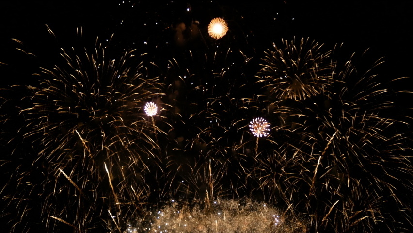 4K long shot 39s. loop seamless of real shining fireworks for celebration background. large golden glowing firework during new year's eve countdown festival in the sky display at night with colorful. Royalty-Free Stock Footage #1064043034