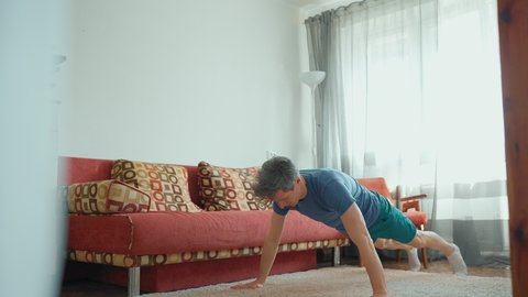 strong muscular man in blue sportswear doing push ups at home. home exercising, healthcare and dobycare concept