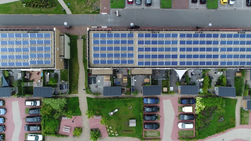 Aerial top down view of new built apartment complex with solar panels installed on the roof from which the photo voltaic cells use sunlight as a source of energy and generate electricity 4k quality Royalty-Free Stock Footage #1064045995