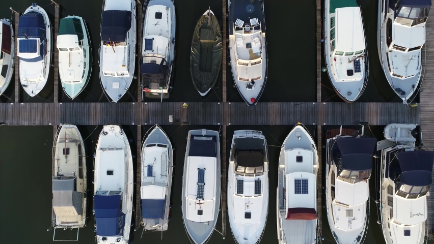 Aerial top down view of marina and docked recreational boats showing the basin with moorings for small vessels it differs from a port because it does not handle large ships or cargo from freighters 4k Royalty-Free Stock Footage #1064045998