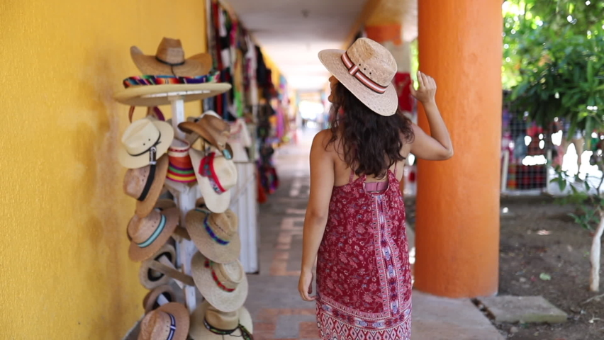 Video of a woman wearing a traditional hat and beach dress and dancing dacing in a colorful shop in Mexico | Shutterstock HD Video #1064046709
