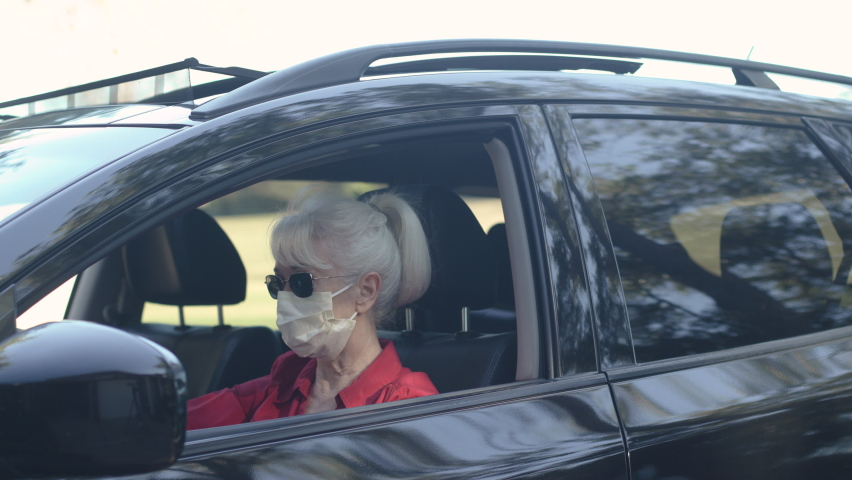 Both individuals masked up due to COVID 19 this woman receives a curbside food delivery from restauranteur who brings it to her vehicle. Royalty-Free Stock Footage #1064047384