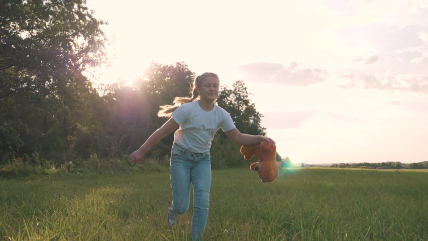 Little girl with a toy teddy bear in park. Cute girl with a teddy bear in a green field. Lonely girl with a toy teddy bear in park in green field.Teddy bear in the hands of a girl in the park Royalty-Free Stock Footage #1064059021