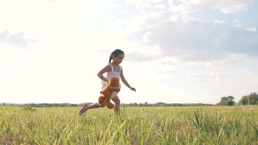 Little girl with a toy teddy bear in park. Cute girl with a teddy bear in a green field. Lonely girl with a toy teddy bear in park in green field.Teddy bear in the hands of a girl in the park Royalty-Free Stock Footage #1064059030