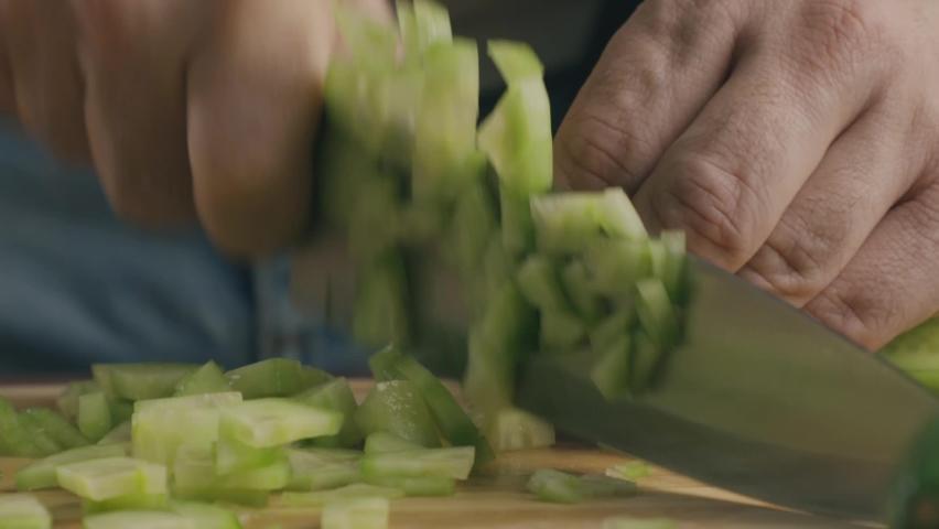 Close up of a man cutting a cucumber in the kitchen | Shutterstock HD Video #1064059045