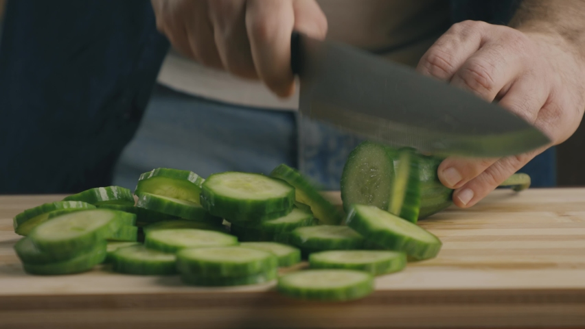 Close up of a man cutting cucumber circles in the kitchen | Shutterstock HD Video #1064059048