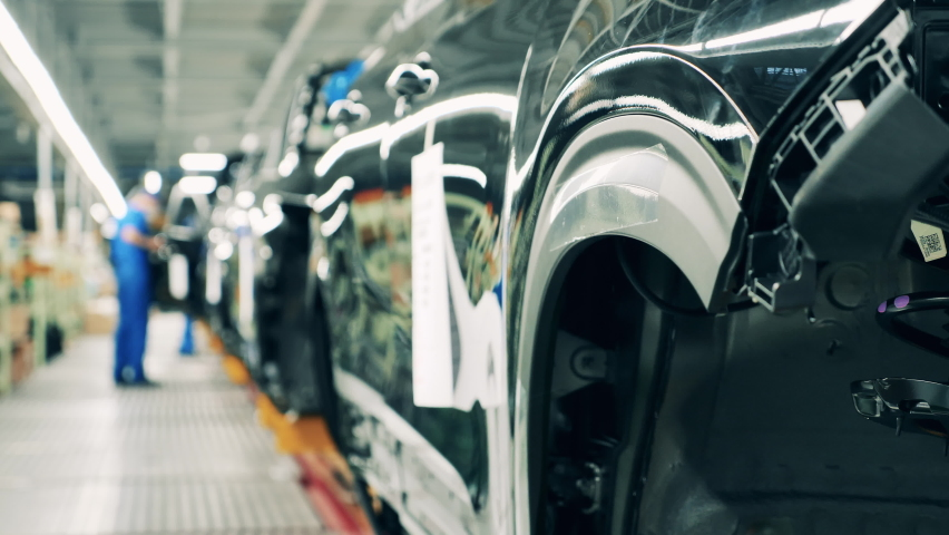 Automobile factory interior. Black colored car body on a car assembly line. Industrial plant, industrial workers at, automobile factory, car production factory facility. Royalty-Free Stock Footage #1064069923