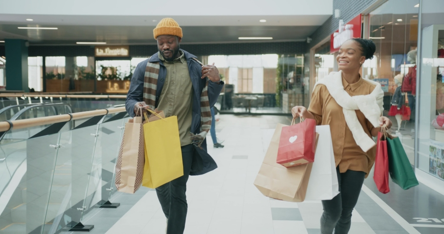 NEW YORK - 19 May 2018: Christmas is coming. Crazy shoppers afro-american young stressful couple shopping for Christmas holidays running in mall sections filled with bags. Funny concept.