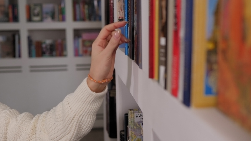 Close-up of a student girl in a white knitted sweater choosing a book in the library on a bookshelf. Royalty-Free Stock Footage #1064105743