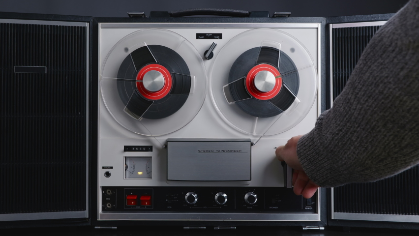 Man hand turns on music on reel to reel tape recorder playing. Rotating vintage music player close up. Retro tape. Spinning reel. Party. Loop. Front view. Front view. Popular Disco Trends 60s, 70s, 80 | Shutterstock HD Video #1064106961