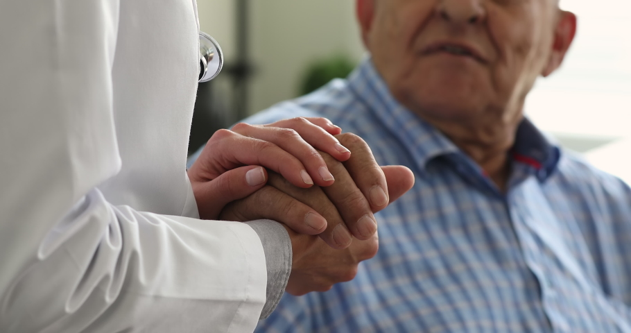 Female doctor in white coat hold 70s senior patient hand for encouragement, express empathy, show support during medicine examination, close up. Medical help, insurance for older, healthcare concept