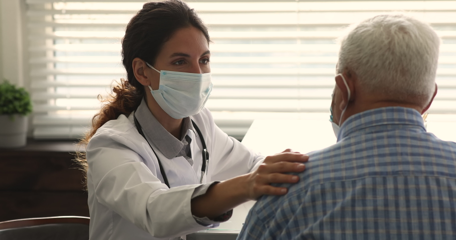 Female doctor wear face mask put hand on older man patient shoulder, talks about upcoming treatment, informs about disease, speaks encouraging speech supporting senior man. Empathy, share pain concept
