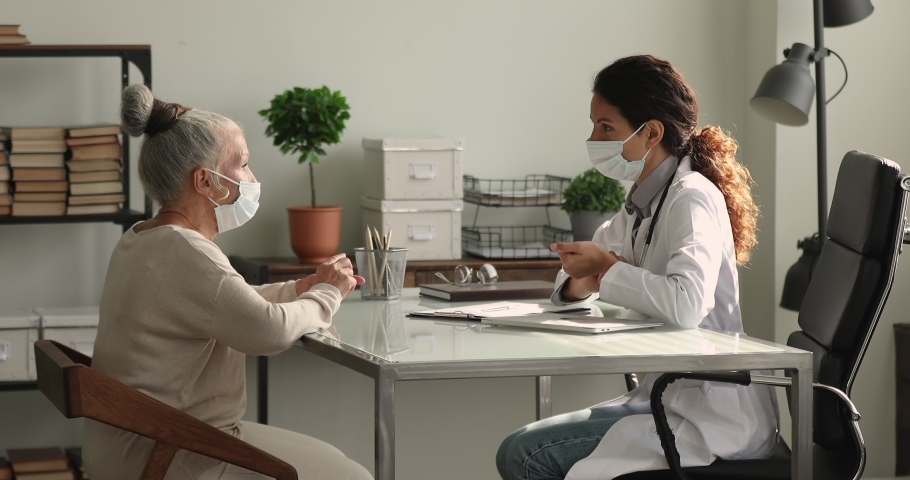 Young therapist and older 65s patient talking and shake hands, due corona virus people wear surgical facemasks for pandemic outbreak precaution. Health check up medical insurance, reliable aid concept Royalty-Free Stock Footage #1064113309