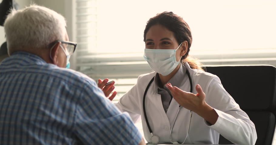 Therapist wear white coat face mask due corona virus pandemic outbreak talk to elderly patient during visit in clinic office, supporting him, telling about health check up, disease treatment concept