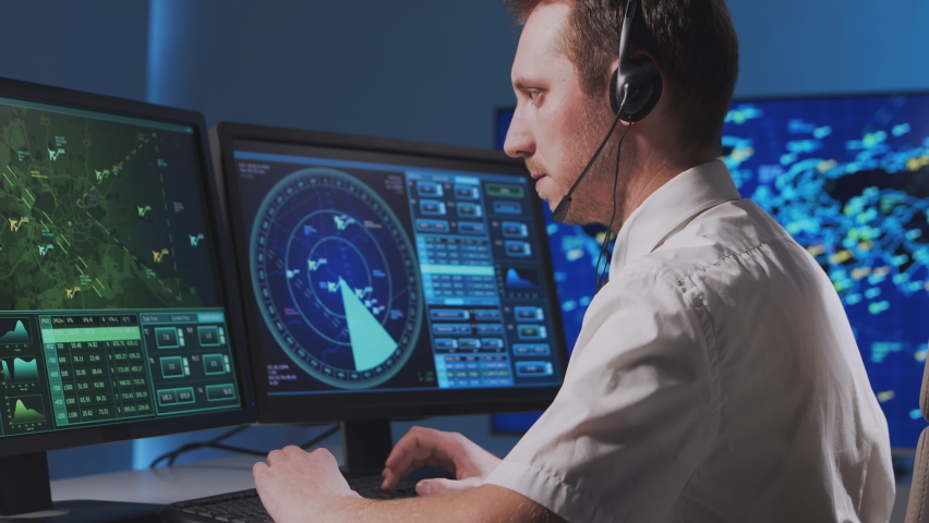 Workplace of the professional air traffic controller in the control tower. Caucasian aircraft control officer works using radar, computer navigation and digital maps.