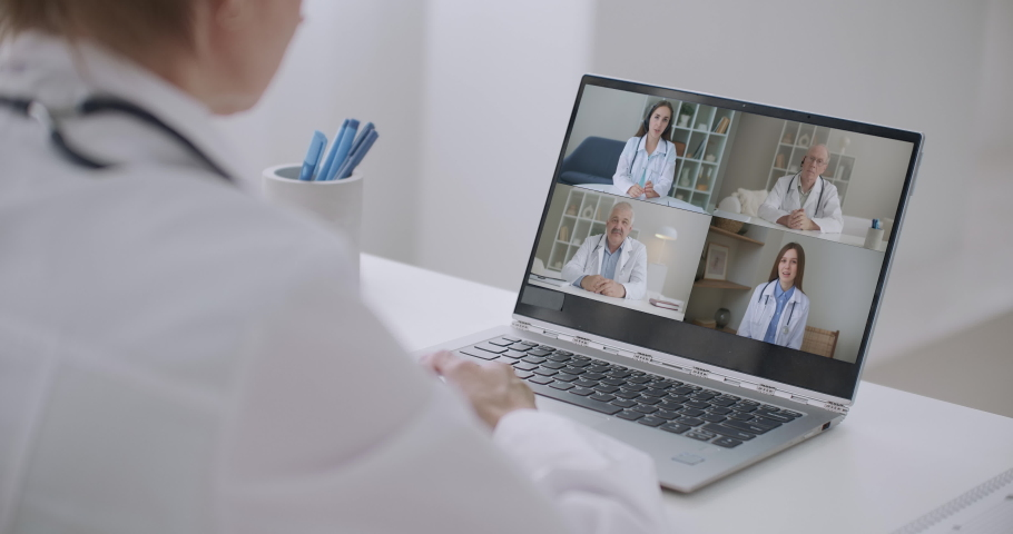 Close up of young female talk on video call consult with diverse doctors colleagues, woman patient have online consultation with GP or physicians, medical nurse in Webcam conference with coworkers   Shutterstock HD Video #1064129047
