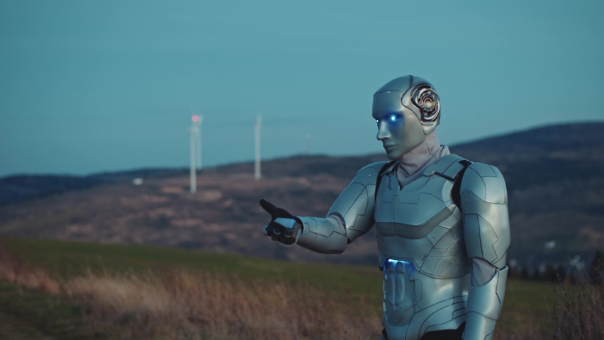 Industrial revolution. Evening view of the robotic blue cyborg using innovative panel with efficiency data graphics animated on his hand outdoor in the field. Agriculture Technology. Future of Farming Royalty-Free Stock Footage #1064129788
