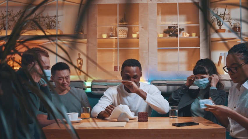Friends gathering in modern cafe. Afro-american sick man sneezes allergy scaring much other people wearing face masks for virus protection. Safety. Influenza. Pandemic. Royalty-Free Stock Footage #1064129965
