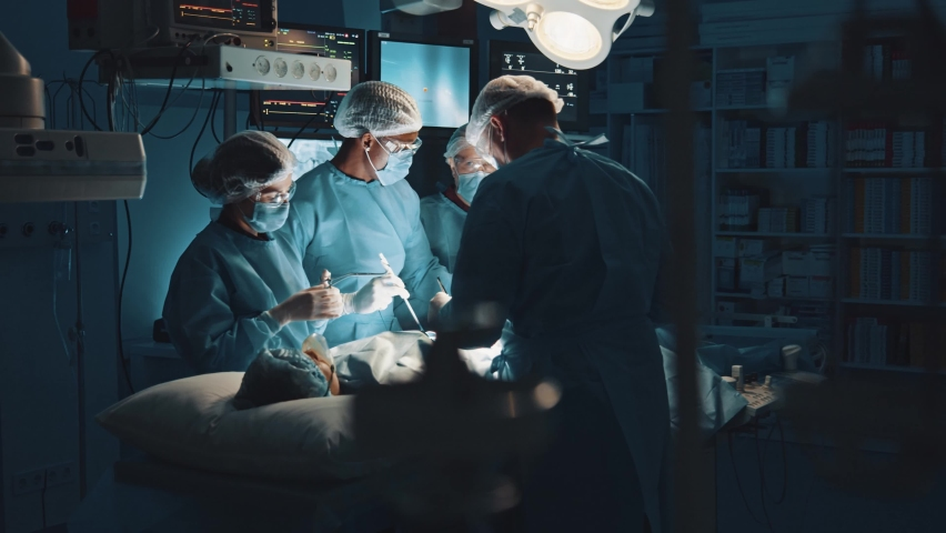 Multi-ethnic cooperating team of doctors and surgeons processing surgical operation in operating room modern hospital emergency department. Heart surgery. | Shutterstock HD Video #1064130013